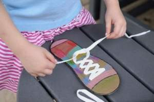 Child tying laces into a bow.